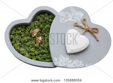 wedding rings in moss in the gray box in the shape of a heart. isolated on white background