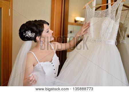 Beautiful Bride In Robe Is Watching A Wedding Dress. Beauty Model Girl In White Clothes. Female Port