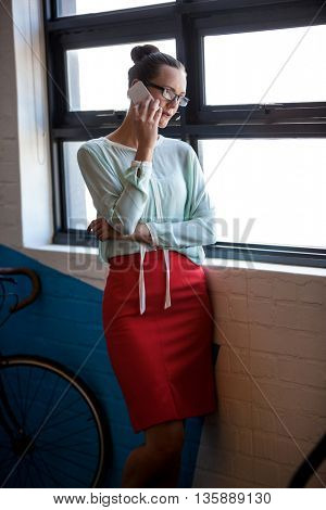 An attractive businesswoman having a phone call in modern studio