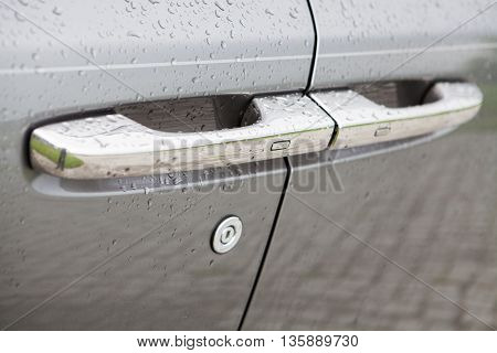 Color image of a car door handle with rain drops.