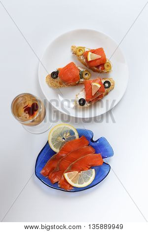 Tasty various italian sandwiches with seafood against white background. Crostini with cheese red fish fillet lemon sliced olives and glass of wine top view