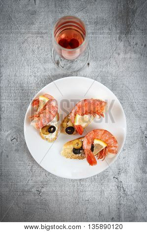 Tasty various italian sandwiches with seafood against rustic wooden background. Crostini with cheese king shrimps lemon sliced olives on white plate and glass of wine top view