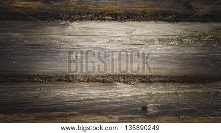 The wall made of wooden logs. The joint between the logs. Background with vignette
