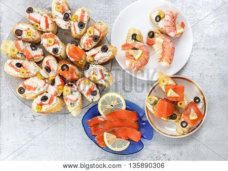 Tasty various italian sandwiches with seafood against rustic wooden background. Crostini with cheese king shrimps mussels red fish crab sticks lemon sliced olives on different plates and slices of red fish fillet horizontal top view
