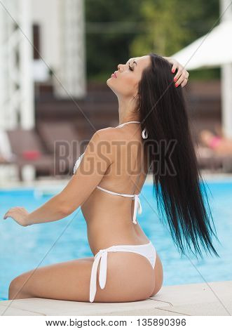 Beautiful sexy young girl with perfect slim figure with long hair and bathing suit sitting on the steps of swimming pool swim, sunbathe, have fun at beach party