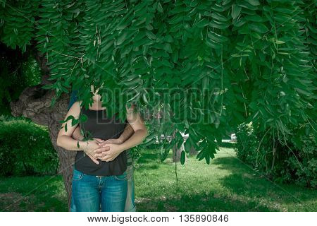 Young couple holding hands under green tree