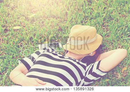 Beautiful young woman with sleeping listen to music in the park,vintage tone