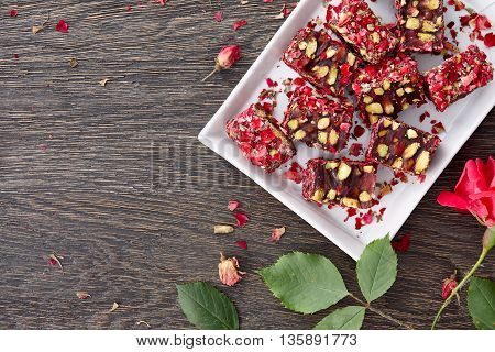 A white rectangular plate full of traditonal turkish delight with rose petals decorated with rose flowers. Dark wooden background, top view.