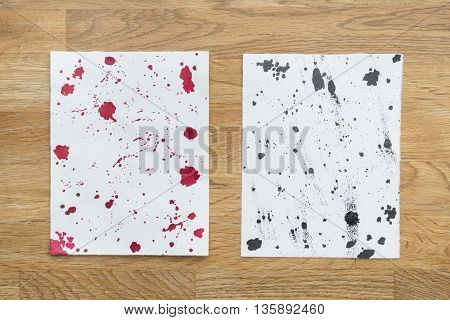 Two piece of papers spotted with ink in a wooden background