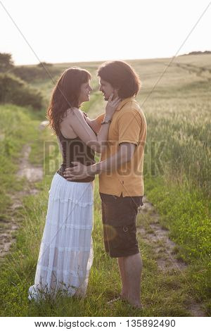 young couple standing in a field. woman hugging a man near a wheat field and they going to kiss each other. concept about passion and love
