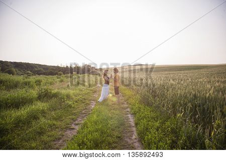 couple in love standing next to each other on the road near the field and touches hands