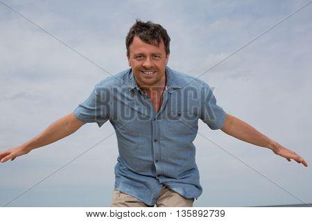 Single Handsome Joyful / Happiness Man Show Hand Up On The Blue Sky Under Sunlight.