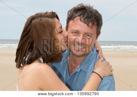 Happy Couple Laughing Together At The Beach Kissing