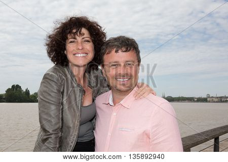 Loving Couple At The River Cuddling Piggy Back