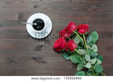 cup of coffee and red roses on table