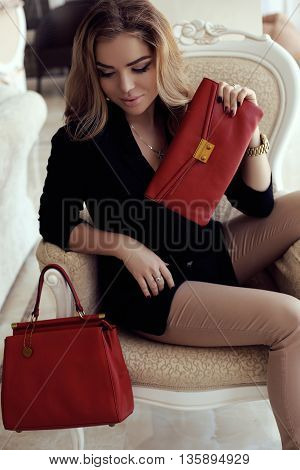 fashion photo of gorgeous woman with dark curly hair in elegant outfit with bag