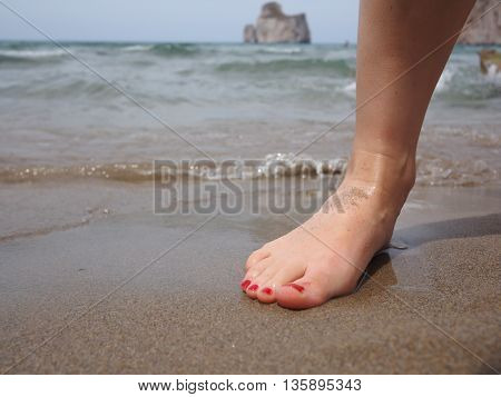 Woman barefoot on the sand with seascape