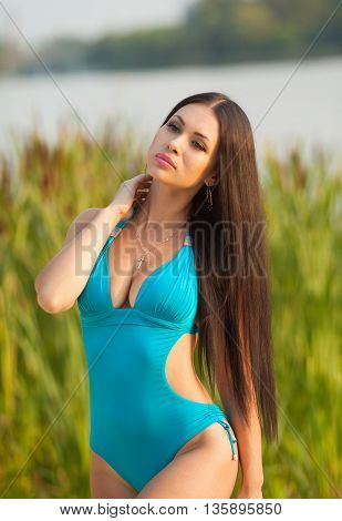 Holiday on the beach. Beautiful young happy brunette woman posing on the beach dressed in swimwear. Enjoys the wind and sun with big smile. Professional make-up, hair style and styling.