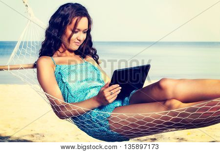 Young Woman Relaxing On Hammock And Using Digital Tablet. Vacation And Travel Concept