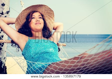 Young Woman Relaxing On Hammock At The Beach. Vacation And Travel Concept