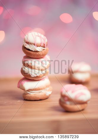 Stack of tasty cakes with cream cheese over colorful lights closeup. Selective focus.