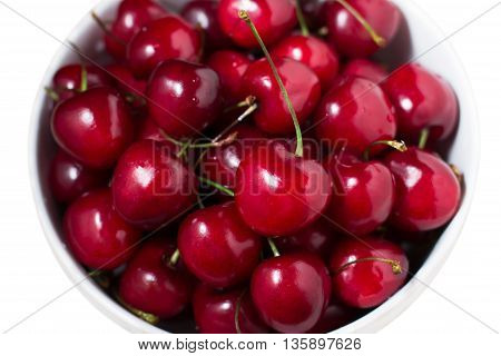 Ripe sweet red cherries in a bowl isolated on white background