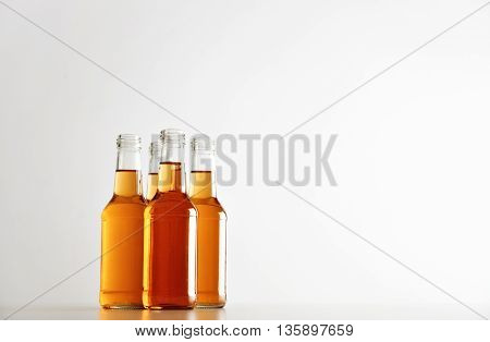 Opened crystal bottles with tasty orange clear drink inside in group isolated on white