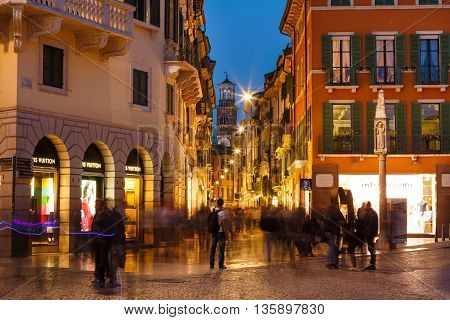 Verona Italy - May 07 2016: Some people walking on the Bra square against the backdrop of the Lamberti tower evening time