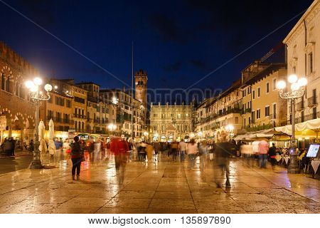 Verona Italy - May 07 2016: Some people walking on the Market square against the backdrop of the Maffei Palace and Gardello tower evening time