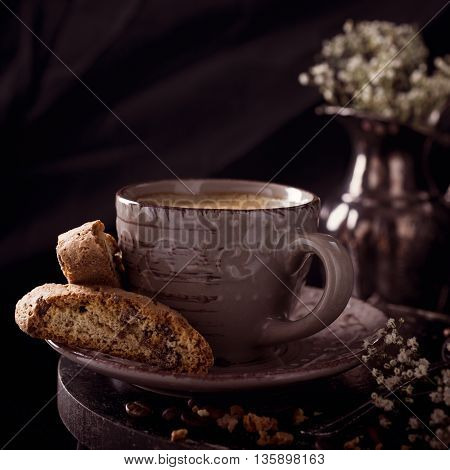 Coffee cup with cookies and coffee beans on dark rustic background with space for text. Toned.