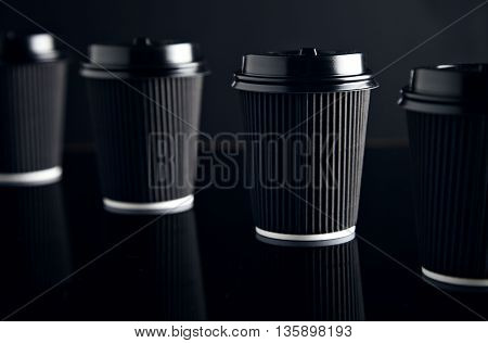Closeup four black take away cardboard paper cups closed with caps isolated on black and mirrored. Retail mockup presentation