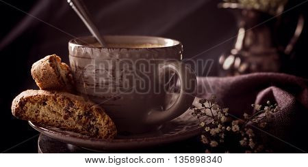 Coffee cup with cookies and coffee beans on dark rustic background. Toned.
