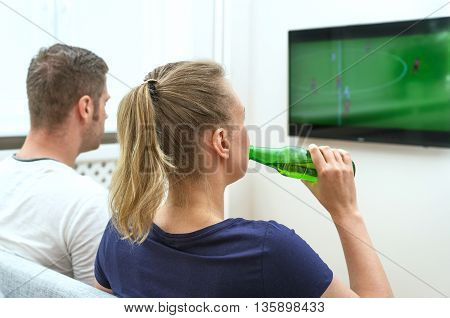 Couple Watching Football Match On Television At Home.