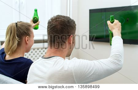 Excited Couple Watching Football Match On Tv.