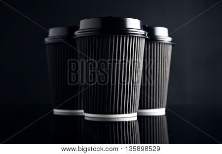 Luxury set of short cardboard paper cups closed with caps isolated on black and mirrored. Retail mockup presentation