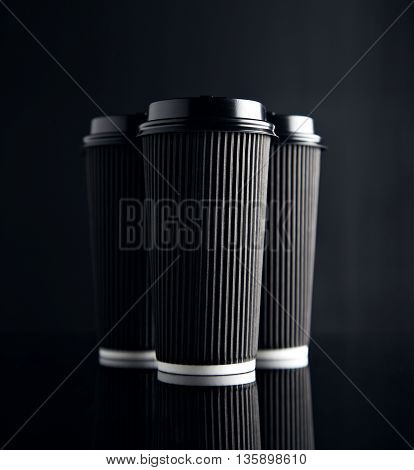 Luxury set of big take away cardboard paper cups closed with caps isolated on black and mirrored. Retail mockup presentation