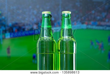 Two bottles of beer in front of TV with football match.