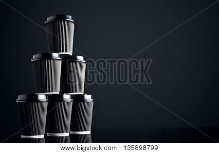 Blank set of black take away cardboard paper cups closed with caps in pyramid shape presented on side, black and mirrored. Retail mockup presentation