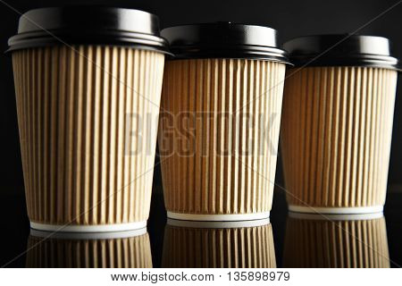 Luxury set of brown take away cardboard paper cups closed with caps isolated on black and mirrored. Retail mockup presentation