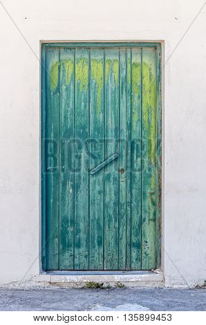 A weathered green doorway on the island of crete