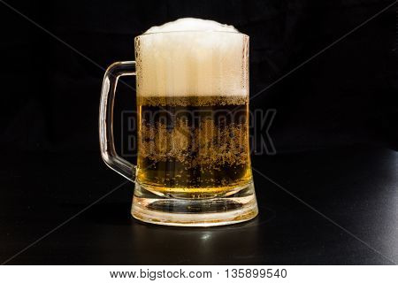 A mug of beer with foam on a black background