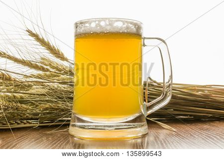 Mug unfiltered beer with barley ears on a white background