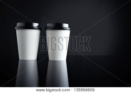 Two take away white cardboard paper cups closed with black caps isolatedon side and mirrored. Retail mockup presentation