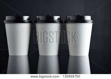 Close view to three take away white cardboard paper cups closed with black caps isolated in center and mirrored. Retail mockup presentation