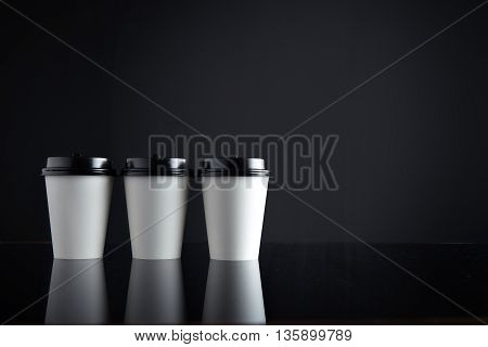 Set of take away white cardboard paper cups closed with black caps isolated on side and mirrored. Retail mockup presentation