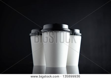 Set of three take away white coffee cardboard paper cups closed with black caps isolated in center and mirrored. Retail mockup presentation