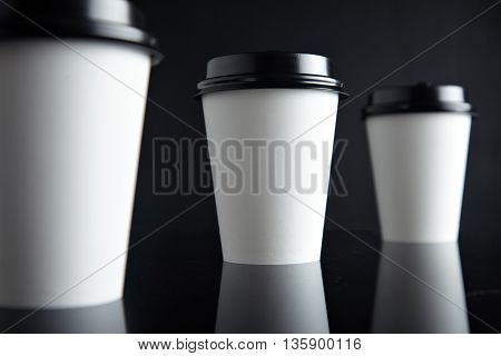 One focused paper cup for hot drinks between two unfocused presented on black back and mirrored, closed with caps