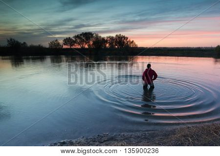 The man costs in the small river and admires a decline. The person looks at a sunset. River at sunset. Ripples in the water.