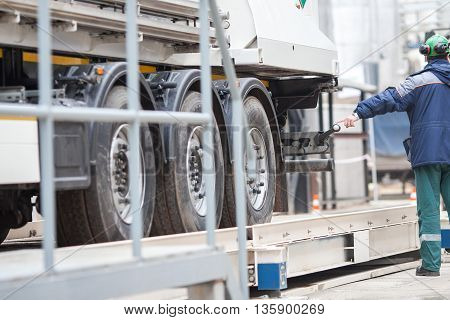 The worker near truck at the industrial enterprise. Men and Tanker Truck In Industrial Plant.