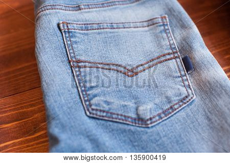 Jeans on wooden background. Blue jeans. Clothes on a brown background.